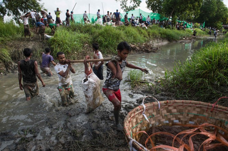 Members of Myanmar's Muslim minority carry rations of meat across a muddy canal during a religious sacrifice of animals in observance of Eid al-Adha on September 13, 2016 in Thanlyin township instead of the town center, a move they said was because of complaints from some Buddhist residents. Muslims across the world are celebrating the annual festival of Eid al-Adha, or the festival of sacrifice, which marks the end of the Hajj pilgrimage to Mecca and commemorates prophet Abraham's readiness to sacrifice his son to show obedience to God. (Romeo Gacad/AFP/Getty Images)