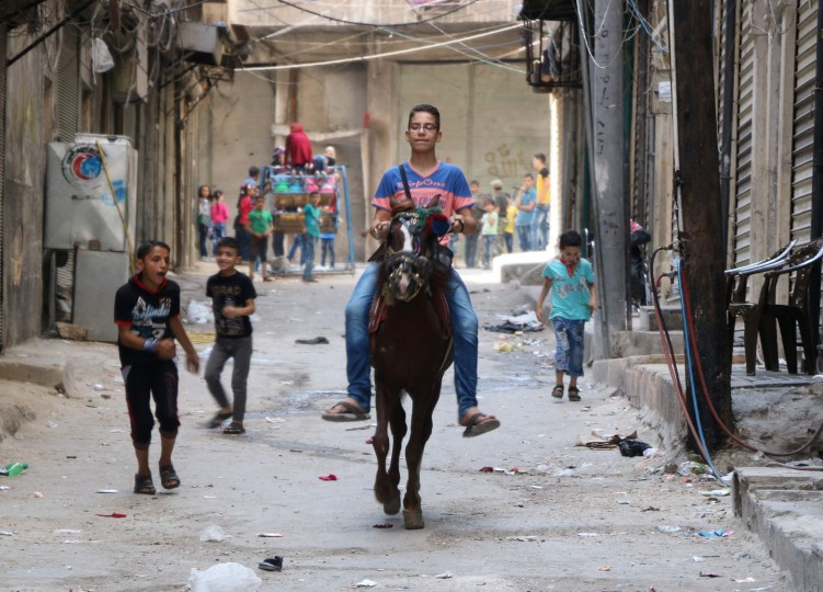 A Syrian boy rides a horse as Syrian children play in the street in the northern Syrian city of Aleppo as they celebrate the Eid al-Adha (Feast of the Sacrifice) holiday on the first day of a fragile ceasefire which aims to bring an end to fighting between loyalists to the Syrian president and a wide range of rebels but excludes jihadist forces like the Islamic State group. AFP correspondents in both the rebel-held east and the government-held west reported nearly 24 hours had passed without air strikes or rocket fire. (Thaer Mohammed/AFP/Getty Images)