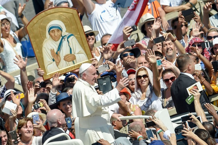 Pope Francis (C) waves to faithful as he leaves after a Holy Mass and the canonisation of Mother Teresa of Kolkata, on Saint Peter square in the Vatican, on September 4, 2016. Mother Teresa, the nun whose work with the dying and destitute of Kolkata made her a global icon of Christian charity, was made a saint on September 4, 2016. Her elevation to Roman Catholicism's celestial pantheon came in a canonisation mass in St Peter's square in the Vatican that was presided over by Pope Francis in the presence of 100,000 pilgrims. (AFP PHOTO / ANDREAS SOLARO)