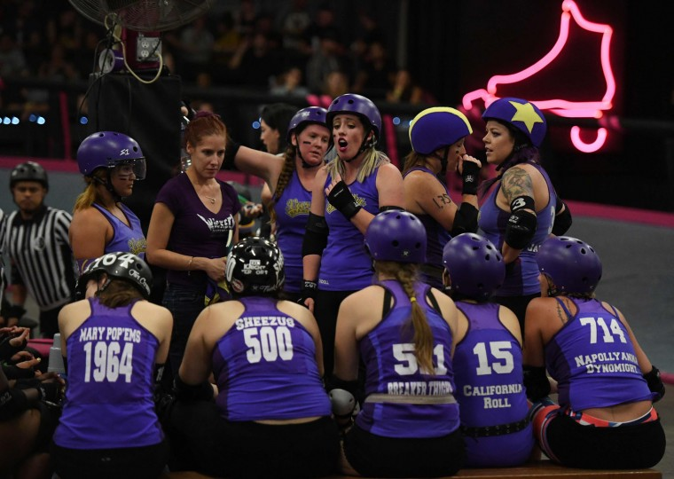Members of the Varsity Brawlers team (purple tops) take a time out as they compete against the Tough Cookies team during the L.A. Derby Dolls women's banked track roller derby event in Los Angeles, California on September 24, 2016. Roller Derby is a contact sport that originated in America and is based on two teams formation roller skating around an oval track, with points scored as one player known as a jammer laps members of the opposing team. The sport, which began in 1922, is played predominantly by women skaters with a strong emphasis on punk aesthetics, unique costumes and humorous stage names. (Mark Ralston/AFP/Getty Images)