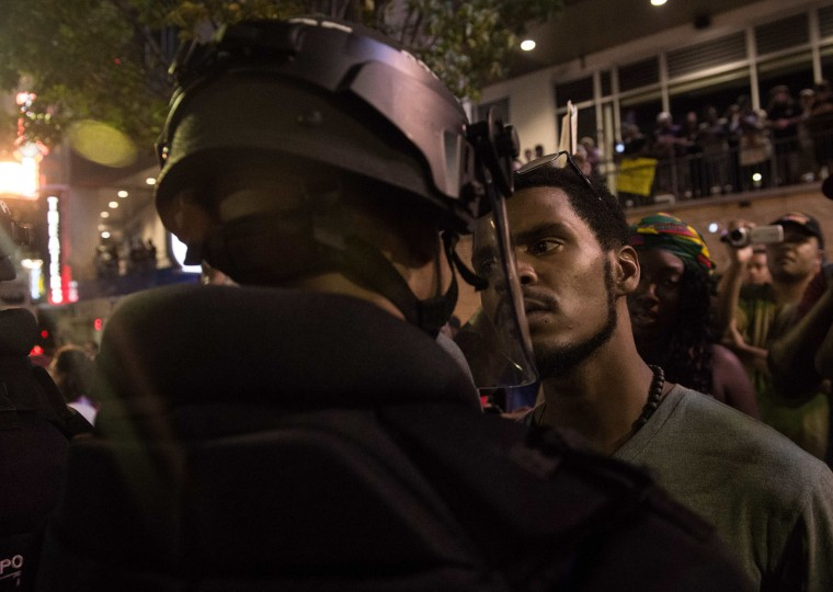 A protester stares at riot police during a demonstration against police brutality in Charlotte, North Carolina, on September 21, 2016, following the shooting of Keith Lamont Scott the previous day. A protester in Charlotte, North Carolina was fatally shot by a civilian during a second night of unrest after the police killed a black man, officials said. (Nicholas Kamm/AFP/Getty Images)