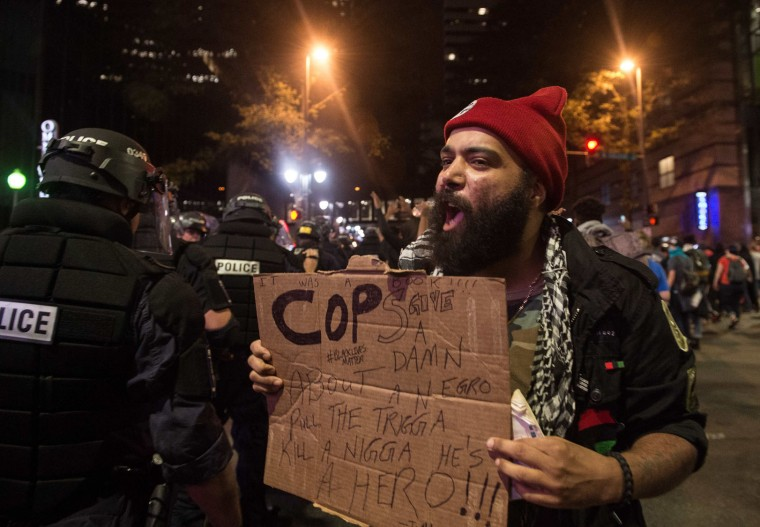 A protester taunts riot police during a demonstration against police brutality in Charlotte, North Carolina, on September 21, 2016, following the shooting of Keith Lamont Scott the previous day. A protester in Charlotte, North Carolina was fatally shot by a civilian during a second night of unrest after the police killed a black man, officials said. (Nicholas Kamm/AFP/Getty Images)