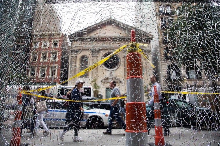 New Yorkers pass a shattered storefront window on W. 23rd St. in Manhattan, Tuesday, Sept. 20, 2016, in New York. The window was hit by shrapnel from the bomb that exploded across the street Saturday evening. An Afghan immigrant wanted in the bombings was captured Monday after being wounded in a gun battle with police. (AP Photo/Mark Lennihan)