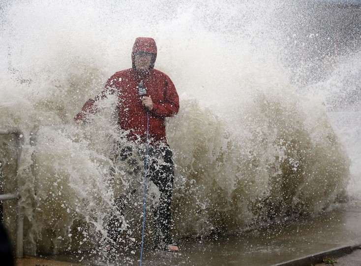 A news reporter doing a stand up near a sea wall in Cedar Key, Fla., is covered by an unexpected wave as Hurricane Hermine nears the Florida coast, Thursday, Sept. 1, 2016. Hurricane Hermine gained new strength Thursday evening and roared ever closer to Florida's Gulf Coast, where rough surf began smashing against docks and boathouses and people braced for the first direct hit on the state from a hurricane in over a decade. (AP Photo/John Raoux)