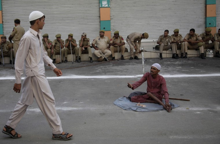 "Security personnel keep guard as a beggar asks for alms to a passing Muslim devout during Eid al-Adha at the Eidgah in Jammu, India, Tuesday, Sept. 13, 2016. Muslims worldwide are celebrating Eid al-Adha, or ""Feast of Sacrifice,"" that commemorates the willingness of the Prophet Ibrahim to sacrifice his son before God stayed his hand. During the holiday, Muslims slaughter livestock and distribute part of the meat to the poor. (AP Photo/Channi Anand)"