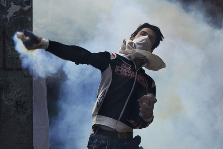 A Kashmiri throws back a tear gas canister at Indian security personnel during a protest after Eid al-Adha prayers in Srinagar, Indian controlled Kashmir, Tuesday, Sept. 13, 2016. Security forces fired tear gas and shotgun pellets to quell protesters in several places, as a security lockdown marred Eid festivities in the troubled region. Shops and businesses were closed, with a curfew in effect in the entire Kashmir Valley. (AP Photo/Dar Yasin)