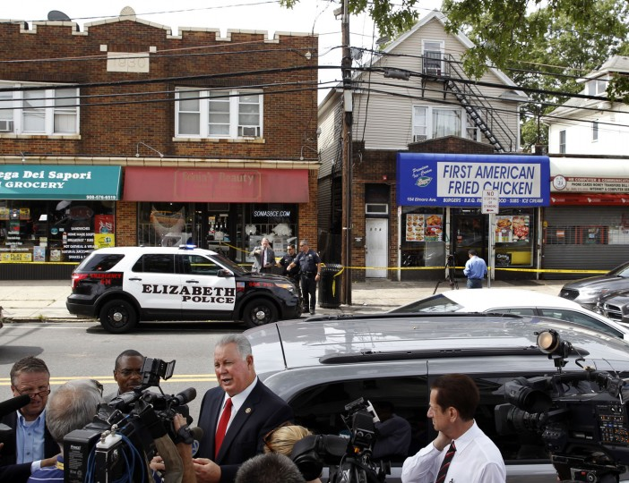 U.S. Rep. Albio Sires, center left, D-8th District, N.J., answers a question as he stands outside the First American Fried Chicken restaurant Tuesday, Sept. 20, 2016, in Elizabeth, N.J. The Elizabeth establishment and the apartment above are tied to Ahmad Khan Rahami, who was arrested as a suspect in the weekend bombings in New York and New Jersey. Sires says Rahami contacted him in 2014 about help with his wife immigrating to the U.S. (AP Photo/Mel Evans)