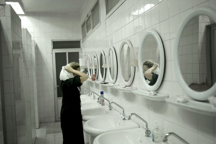 "In this Tuesday, Sept. 13, 2016 photo, 36-year old Dalia from Lebanon takes off her hijab to start performing Wudu, a ritual of washing before prayer, inside an only women's camp in Mina, Saudi Arabia. ""I am not convinced that hijab is a must and sign of faith. I have been treating people with what I believe is ethical and human. I will continue to do so after the hajj. The Hajj was an opportunity though to look deep into myself and rediscover my faith and maybe to recall its importance in my life. I learned again how to pray after I stopped for more than 25 years,"" says Dalia on her experience during the hajj. (AP Photo/Nariman El-Mofty)"