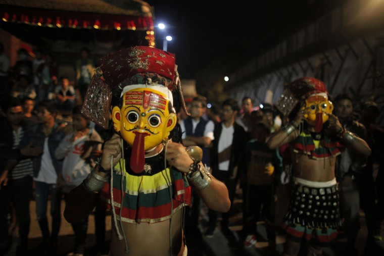 Masked dancers prepare to perform a traditional dance during Indra Jatra Festival in Basantapur Durbar Square, Kathmandu, Nepal, Friday, Sept. 16, 2016. Indra is considered the Hindu god of rain and the festival marks the end of the rainy season. (AP Photo/Niranjan Shrestha)