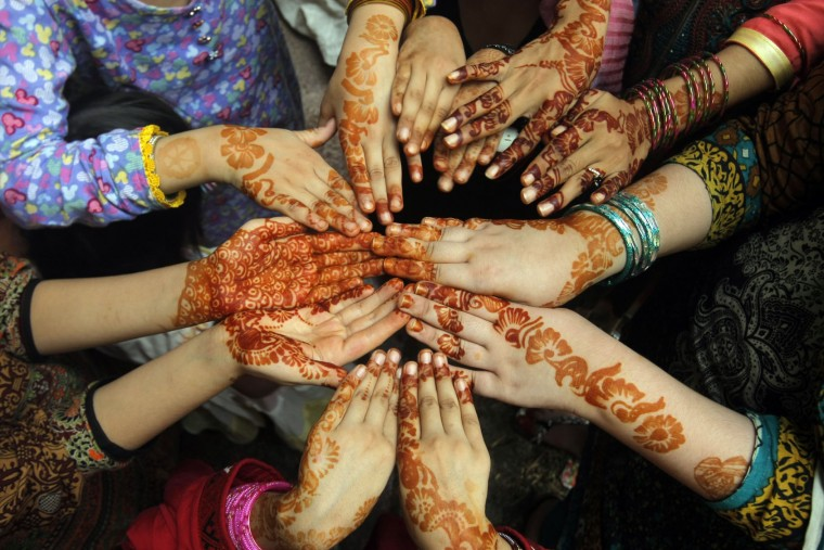 Pakistani women show their hands decorated with henna during celebrations for the Muslim Eid al Adha holiday, in Peshawar, Pakistan, Tuesday, Sept. 13, 2016. Pakistani Muslims are celebrating Eid al-Adha, or the Feast of the Sacrifice, to mark the willingness of the Prophet Ibrahim -- Abraham to Christians and Jews -- to sacrifice his son. During the holiday Muslims slaughter sheep and cattle and distribute part of the meat to the poor. (AP Photo/Mohammad Sajjad)