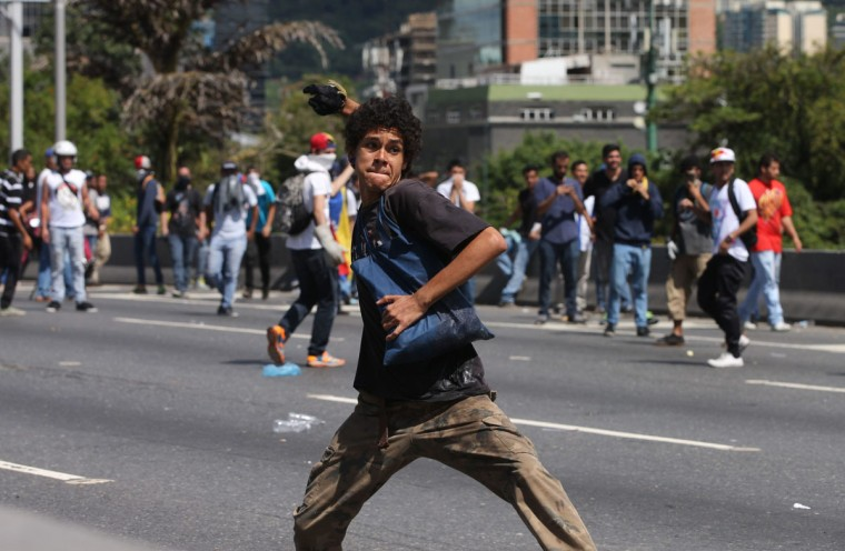 "An anti-government demonstrator winds up to throw a stone at police, during the ""taking of Caracas"" march in Caracas, Venezuela, Thursday, Sept. 1, 2016. Venezuela's opposition is vowing to keep up pressure on President Nicolas Maduro after flooding the streets of Caracas with demonstrators Thursday in its biggest show of force in years. Protesters filled dozens of city blocks in what was dubbed the ""taking of Caracas"" to pressure electoral authorities to allow a recall referendum against Maduro this year. (AP Photo/Fernando Llano)"