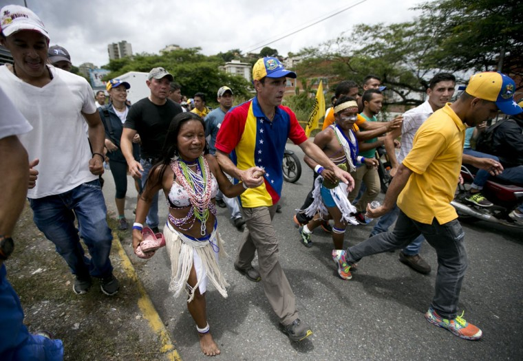 "Venezuela's opposition leader Henrique Capriles holds hands with a Piaroa Indian woman as they walk in the ""taking of Caracas"" march in Caracas, Venezuela, Thursday, Sept. 1, 2016. Venezuela's opposition is vowing to keep up pressure on President Nicolas Maduro after flooding the streets of Caracas with demonstrators Thursday in its biggest show of force in years. Protesters filled dozens of city blocks in what was dubbed the ""taking of Caracas"" to pressure electoral authorities to allow a recall referendum against Maduro this year. (AP Photo/Ariana Cubillos)"