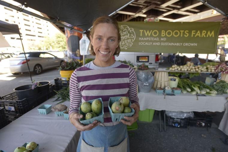 Elisa Lane sells pawpaws at the Sunday Farmers' Market in Baltimore. (Christina Tkacik/Baltimore Sun)
