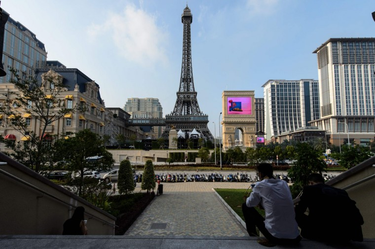 People look at a replica of the Eiffel Tower ahead of the opening of the Sands new mega resort The Parisian in Macau on September 13, 2016. Casino giant Las Vegas Sands launched Macau's latest resort on September 13, outfitted with a half-size replica of the Eiffel Tower, as it bets its fortunes on mass market tourists flocking to the gambling enclave.(ANTHONY WALLACE/AFP/Getty Images)
