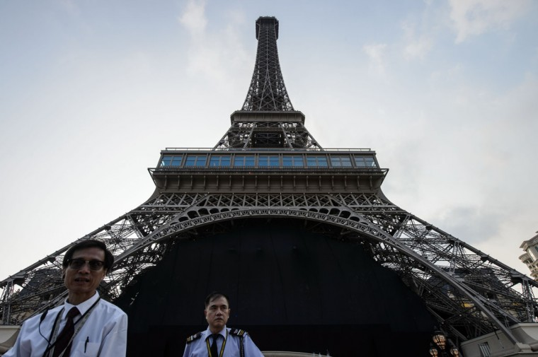 Members of security stand guard in front of a replica of the Eiffel Tower ahead of the opening of the Sands new mega resort The Parisian in Macau on September 13, 2016. (ANTHONY WALLACE/AFP/Getty Images)