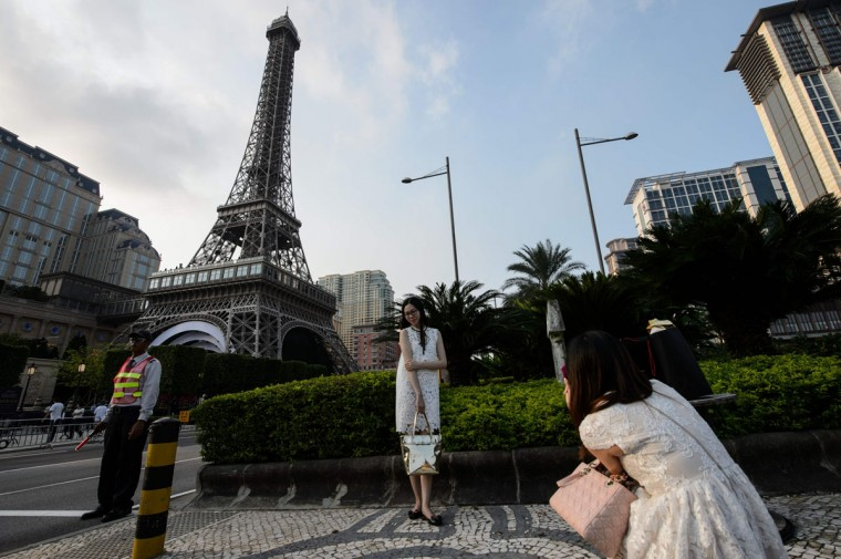 Pedestrians pose in front of a replica of the Eiffel Tower ahead of the opening of the Sands new mega resort The Parisian in Macau on September 13, 2016. (ANTHONY WALLACE/AFP/Getty Images)