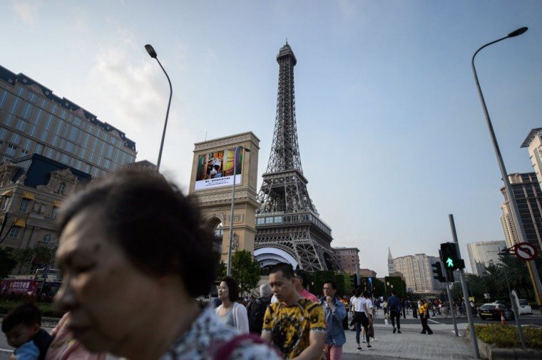 Pedestrians walk past a replica of the Eiffel Tower ahead of the opening of the Sands new mega resort The Parisian in Macau on September 13, 2016. (ANTHONY WALLACE/AFP/Getty Images)