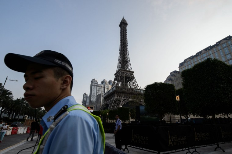 Members of security stand guard in front of a replica of the Eiffel Tower ahead of the opening of the Sands new mega resort The Parisian in Macau on September 13, 2016. Casino giant Las Vegas Sands launched Macau's latest resort on September 13, outfitted with a half-size replica of the Eiffel Tower, as it bets its fortunes on mass market tourists flocking to the gambling enclave. (ANTHONY WALLACE/AFP/Getty Images)