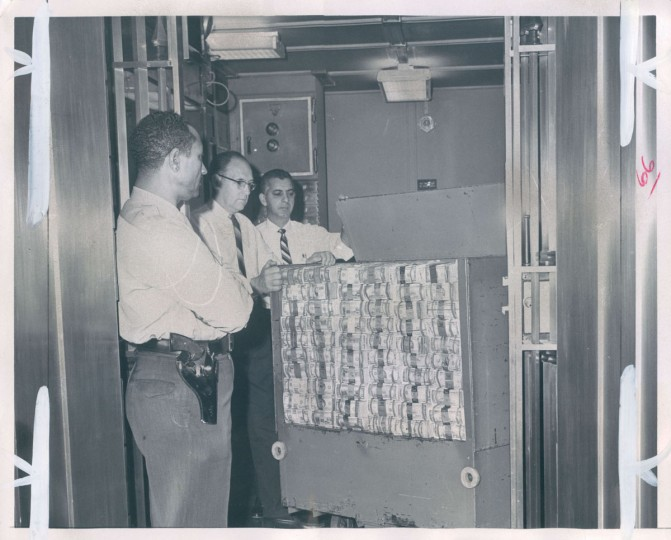 """""""There's $3,000,000 here,"""" read the caption to this 1967 photo. """"This is only a part of the bundles of bills which daily move into and out of the Federal Reserve Bank branch as it supplies Maryland banks with the necessary cash to conduct business. Left to right--Julius H. Pryor, a guard; Edward Gluth and S.J. Sinnicchio."""" (Gardina/Baltimore Sun)"""