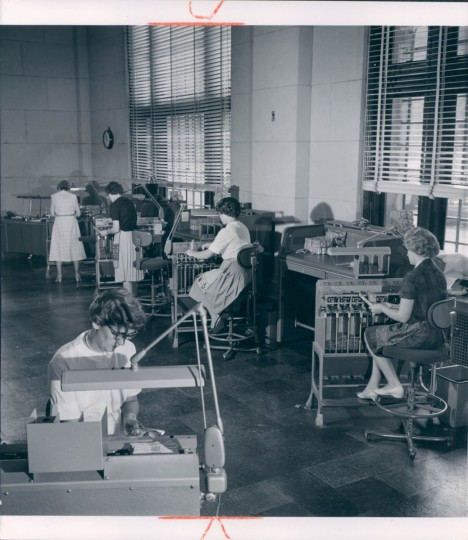 """The counting room in the old Federal Reserve Bank in Baltimore, seen in 1961. """"Despite the speed with which they handle the huge numbers of bills, the girls can spot bogus ones instantly,"""" reads the caption. (Richard Stacks/Baltimore Sun)"""