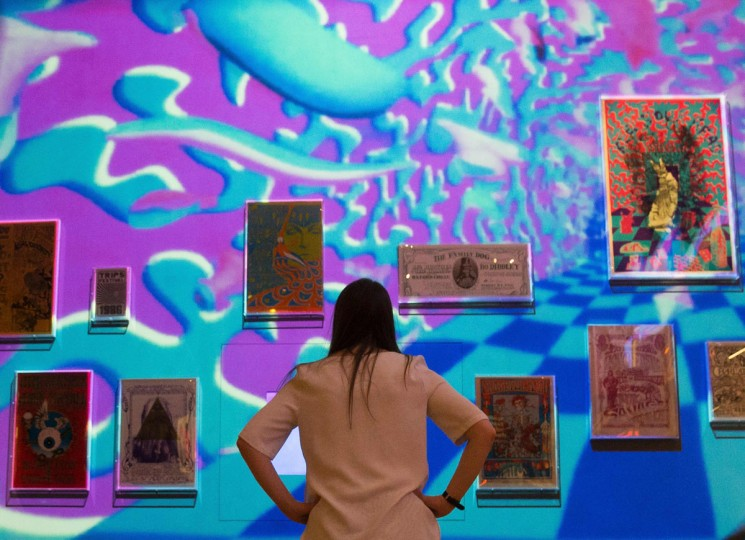A V&A employee poses in front of a psychedelic projection looking at framed posters during a photo-call for the You Say You Want a Revolution? Records and Rebels 1966-70 exhibition at the V&A museum in central London on September 7, 2016. The exhibition that aims to trace the significance and impact of the late 1960s on life today opens on September 10. (DANIEL LEAL-OLIVAS/AFP/Getty Images)