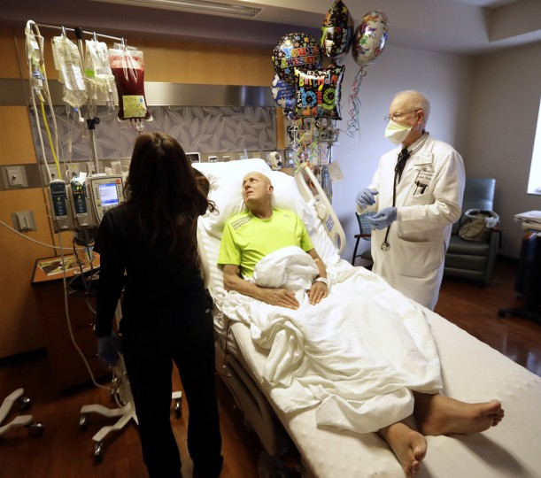 Sportscaster Craig Sager, center, watches as nurse Diana Castillo, left, and Dr. Richard Champlin, right, start the transplant procedure Wednesday, Aug. 31, 2016, at MD Anderson Hospital in Houston. Sager underwent his third bone marrow transplant Wednesday as he continues to battle acute myeloid leukemia. (AP Photo/David J. Phillip)
