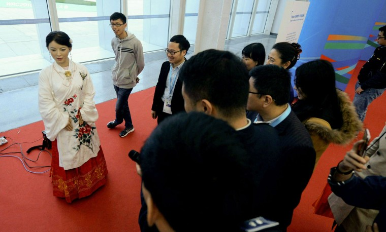 This photo taken on October 20, 2016 shows visitors watching a humanoid robot speaking during the 2016 World Robot Conference in Beijing. More than 2,000 contestants from different countries and regions take part in the conference on October 20 to 25. (STR/AFP/Getty Images)