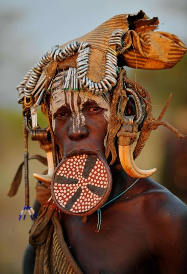 "A woman from the Mursi tribe poses for a photo in the Mago National park near Jinka in Ethiopia's southern Omo Valley region on September 21, 2016. The Mursi are a Nilotic pastoralist ethnic group which number around 10,000 people in Ethiopia. Some Mursi women choose to wear a saucer lip plate (dhebi a tugoin). A girls lower lip is cut when she reaches the age of 15 or 16. The wound is then stretched over time to accomodate a large clay plate. The Mursi tribe are one of the few tribes left who continue this practise. The construction of a sugar factory in Mago National Park has begun to change the way of life for many Mursi as they begin to leave their traditional way of life to work at the factory. Human rights groups also report that the Mursi fear eviction by the Ethiopian government from a large area of the park altogether. The construction of the Gibe III dam, the third largest hydroelectric plant in Africa, and large areas of very ""thirsty"" cotton and sugar plantations and factories along the Omo river are impacting heavily on the lives of tribes living in the Omo Valley who depend on the river for their survival and way of life. Human rights groups fear for the future of the tribes if they are forced to scatter, give up traditional ways through loss of land or ability to keep cattle as globalisation and development increases. (AFP PHOTO / CARL DE SOUZA)"