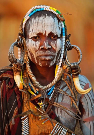 "A woman from the Mursi tribe poses for a photo in the Mago National park near Jinka in Ethiopia's southern Omo Valley region on September 21, 2016. The Mursi are a Nilotic pastoralist ethnic group which number around 10,000 people in Ethiopia. Some Mursi women choose to wear a saucer lip plate (dhebi a tugoin). A girls lower lip is cut when she reaches the age of 15 or 16. The wound is then stretched over time to accomodate a large clay plate. The Mursi tribe are one of the few tribes left who continue this practise. The construction of a sugar factory in Mago National Park has begun to change the way of life for many Mursi as they begin to leave their traditional way of life to work at the factory. Human rights groups also report that the Mursi fear eviction by the Ethiopian government from a large area of the park altogether. The construction of the Gibe III dam, the third largest hydroelectric plant in Africa, and large areas of very ""thirsty"" cotton and sugar plantations and factories along the Omo river are impacting heavily on the lives of tribes living in the Omo Valley who depend on the river for their survival and way of life. Human rights groups fear for the future of the tribes if they are forced to scatter, give up traditional ways through loss of land or ability to keep cattle as globalisation and development increases. / (AFP PHOTO / CARL DE SOUZA)"