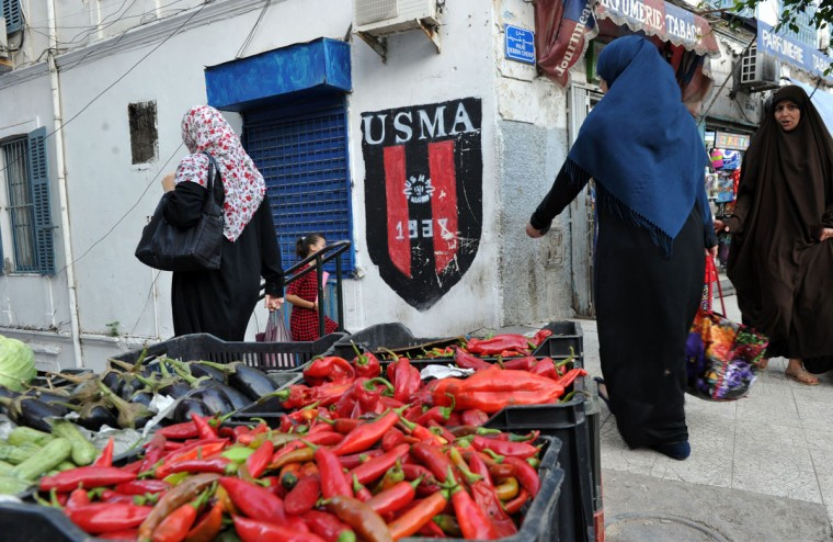"Algerian women walk past a shop bearing the colors of the Union Sportive Medina d'Alger (USMA) football club in the Soustara neighborhood, in the old part of Algiers known as the ""Casbah"", which is historically known to be predominantly supporting USMA, on October 11, 2016, two days ahead of the 100th derby match against their rival Mouloudia Club d'Alger (MCA). (AFP PHOTO / Ryad Kramdi)"