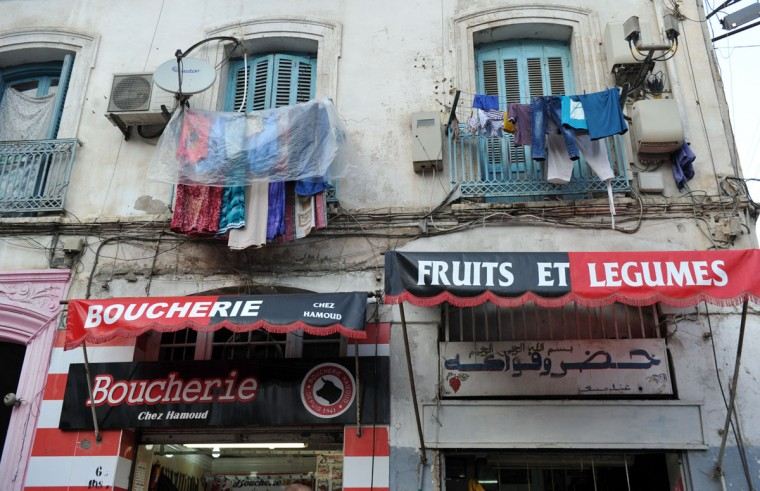 "Clothes hang above shops bearing the colors of the Union Sportive Medina d'Alger (USMA) football club in the Soustara neighborhood in the old part of Algiers known as the ""Casbah"", which is historically known to be predominantly supporting USMA, in Algiers on October 11, 2016, two days ahead of the 100th derby match against their rival Mouloudia Club d'Alger (MCA). (AFP PHOTO / Ryad Kramdi)"