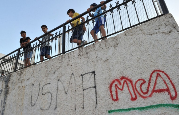 Algerian children play in the street in the Bab el-Oued neighborhood, which is historically known to be predominantly supporting Mouloudia Club Alger (MCA) football team in Algiers on October 11, 2016, two days ahead of the 100th derby match against their rival Union Sportive Medina d'Alger (USMA). (AFP PHOTO / Ryad Kramdi)