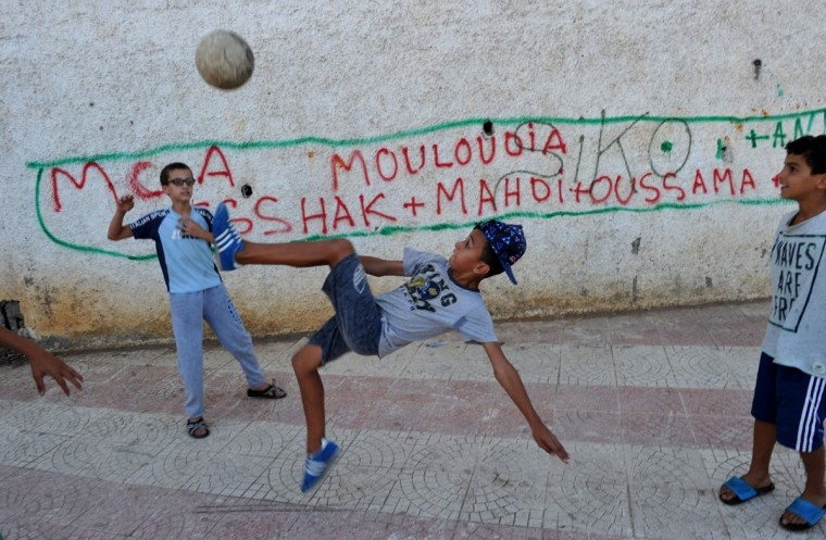 Algerian children play football in the street in the Bab el-Oued neighborhood, which is historically known to be predominantly supporting Mouloudia Club Alger (MCA) football team in Algiers on October 11, 2016, two days ahead of the 100th derby match against their rival Union Sportive Medina d'Alger (USMA). (AFP PHOTO / Ryad Kramdi)