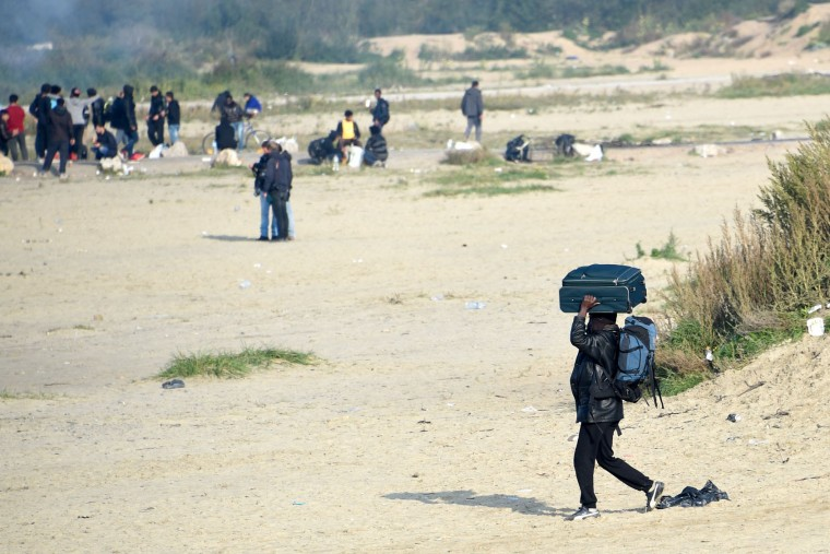 "A migrant, carrying his luggage, leave during the full evacuation of the Calais ""Jungle"" camp, in Calais, northern France, on October 25, 2016. More than 1,900 left the slum on October 24, ahead of work to tear down the makeshift shelters and eateries in the camp that has become a symbol of Europe's refugee crisis. (Denis Charlet/AFP/Getty Images)"