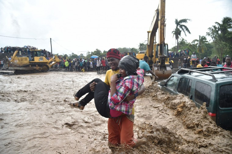 A woman is carried across the river La Digue in Petit Goave where the bridge collapsed during the rains of the Hurricane Matthew, southwest of Port-au-Prince, October 5, 2016. Haiti and the eastern tip of Cuba -- blasted by Matthew on October 4, 2016 -- began the messy and probably grim task of assessing the storm's toll. Matthew hit them as a Category Four hurricane but has since been downgraded to three, on a scale of five, by the US National Hurricane Center. (Hector Retamal/AFP/Getty Images)