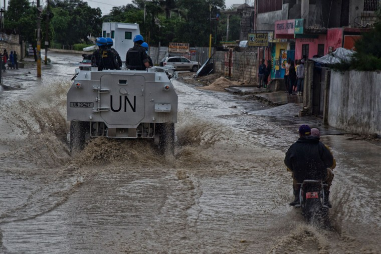 In this photo released by UNICEF, Brazilian peacekeepers with the UN Force Commander conduct a patrol along a flooded road as hurricane Matthew passes over on October 4, 2016 Port au Prince. Weakened but still dangerous, Hurricane Matthew churned toward the Bahamas Wednesday en route to an already jittery Florida after killing at least nine people in the Caribbean in a maelstrom of wind, mud and water. (AFP Photo/UNICEF/Igor Rugwiza)