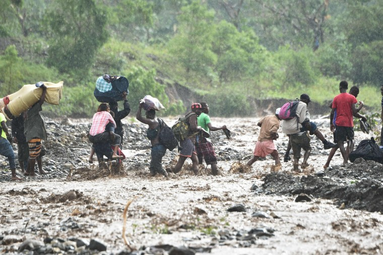 Haitian people cross the river La Digue in Petit Goave where the bridge collapsed during the rains of the Hurricane Matthew, southwest of Port-au-Prince, October 5, 2016. Haiti and the eastern tip of Cuba -- blasted by Matthew on October 4, 2016 -- began the messy and probably grim task of assessing the storm's toll. Matthew hit them as a Category Four hurricane but has since been downgraded to three, on a scale of five, by the US National Hurricane Center. (Hector Retamal/AFP/Getty Images)