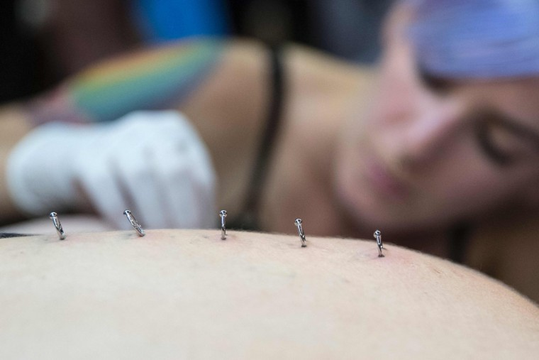 A piercing artist poses piercing on the back of a woman during the Israel Tattoo Convention in the Israeli coastal city of Tel Aviv, on October 07, 2016. Thousands of people are coming to visit today as over 140 tattoo artists from around the world showcase their work on the first day of the 4th Israel Tattoo Convention. / (AFP Photo/Jack Guez)