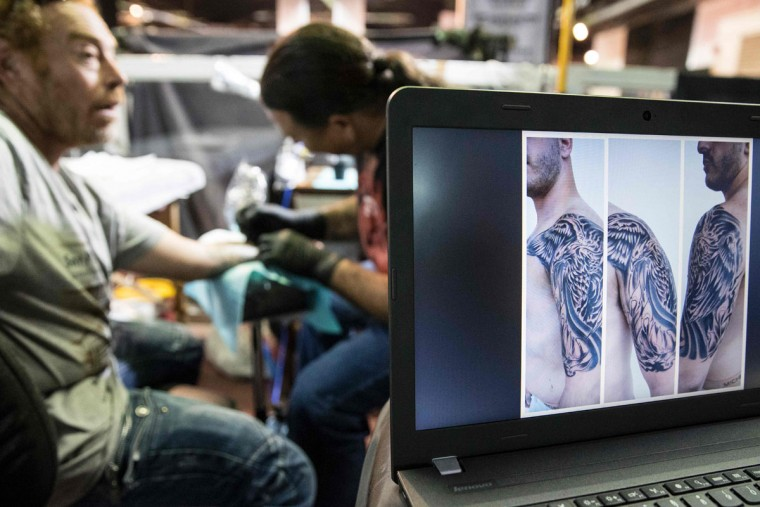 A man receives a tattoo on his arm at the Israel Tattoo Convention in the Israeli coastal city of Tel Aviv on October 07, 2016. Thousands of people are coming to visit today as over 140 tattoo artists from around the world showcase their work on the first day of the 4th Israel Tattoo Convention. / (AFP Photo/Jack Guez)