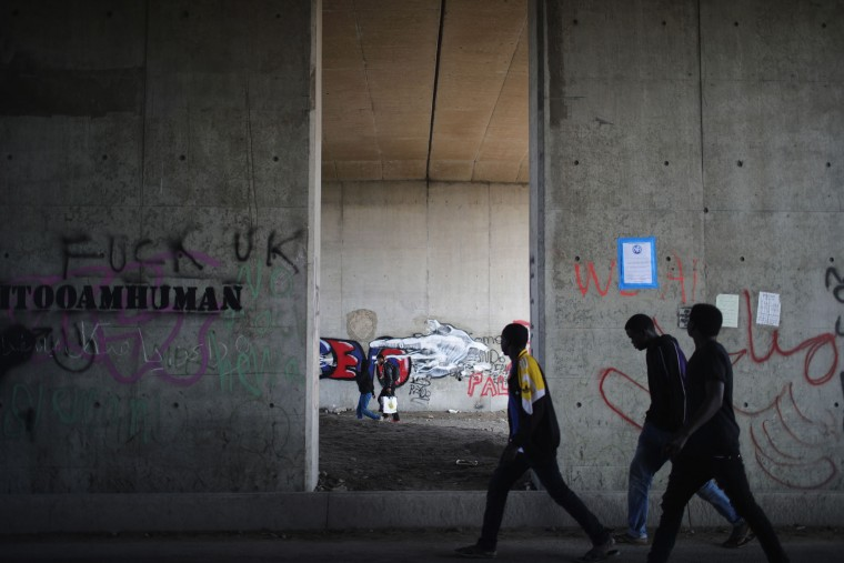 Migrants walk under the motorway as they leave the notorious 'Jungle' camp as the authorities begin the task of demolishing the site on October 25, 2016 in Calais, France. Many migrants have left by coach to be reloctated at centres across France as Police and officials in France begin to clear the 'Jungle' migrant camp in Calais. Some 7,000 people are estimated to be living in the camp in squalid conditions. (Photo by Christopher Furlong/Getty Images)