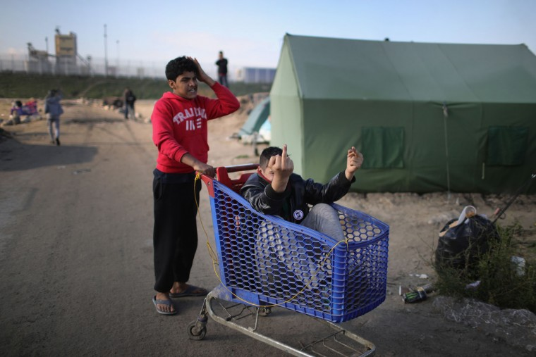 Young migrants play to the camera at the notorious 'Jungle' camp as the authorities begin the task of demolishing the site on October 25, 2016 in Calais, France. Many migrants have left by coach to be relocated at centres across France as Police and officials in France begin to clear the 'Jungle' migrant camp in Calais. Some 7,000 people are estimated to be living in the camp in squalid conditions. (Photo by Christopher Furlong/Getty Images)