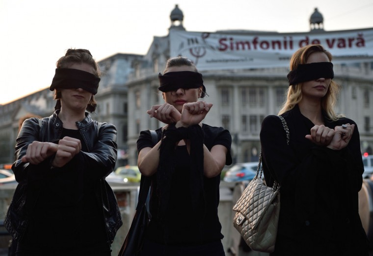 "Romanian woman show support with Polish women on strike during a flashmob in Piata Universitatii square in Bucharest on October 3, 2016. Thousands of women dressed in black protested across Poland in the ""Women strike"" campaign against a proposed near-total abortion ban in the devoutly Catholic country where legislation is already among the most restrictive in Europe. (Daniel Mihailescu/AFP/Getty Images)"