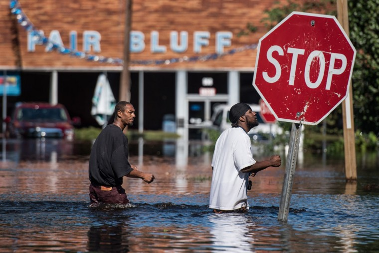FAIR BLUFF, NC - OCTOBER 11: Vance Barden, left, and Wayne Edwards walk through a flooded street caused by remnants of Hurricane Matthew on October 11, 2016 in Fair Bluff, North Carolina. Thousands of homes have been damaged in North Carolina as a result of the storm and many are still under threat of flooding. (Photo by Sean Rayford/Getty Images)