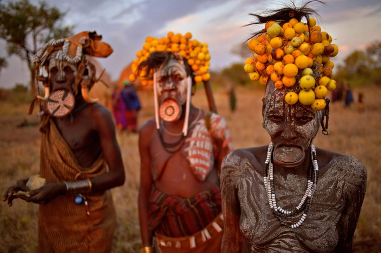 "Women from the Mursi tribe pose for a photo in the Mago National park near Jinka in Ethiopia's southern Omo Valley region on September 21, 2016. The Mursi are a Nilotic pastoralist ethnic group which number around 10,000 people in Ethiopia. Some Mursi women choose to wear a saucer lip plate (dhebi a tugoin). A girls lower lip is cut when she reaches the age of 15 or 16. The wound is then stretched over time to accomodate a large clay plate. The Mursi tribe are one of the few tribes left who continue this practise. The construction of a sugar factory in Mago National Park has begun to change the way of life for many Mursi as they begin to leave their traditional way of life to work at the factory. Human rights groups also report that the Mursi fear eviction by the Ethiopian government from a large area of the park altogether. The construction of the Gibe III dam, the third largest hydroelectric plant in Africa, and large areas of very ""thirsty"" cotton and sugar plantations and factories along the Omo river are impacting heavily on the lives of tribes living in the Omo Valley who depend on the river for their survival and way of life. Human rights groups fear for the future of the tribes if they are forced to scatter, give up traditional ways through loss of land or ability to keep cattle as globalisation and development increases. / (AFP PHOTO / CARL DE SOUZA)"