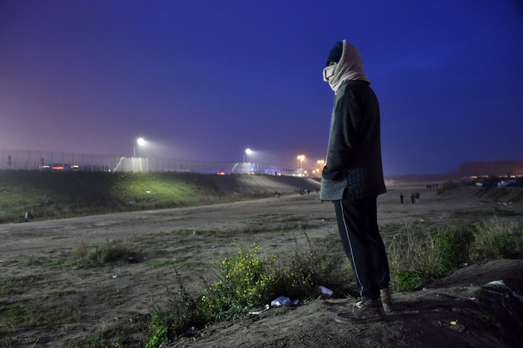 "A migrant looks on at the ""Jungle"" migrant camp in Calais, northern France, early on October 24, 2016, as an evacuation operation is planned to clear the camp of its estimated 6,000-8,000 occupants. French authorities are set to begin on October 24, 2016 moving thousands of people out of the notorious Calais Jungle before demolishing the camp that has served as a launchpad for attempts to sneak into Britain. The current Jungle camp dates from April 2015 and housed more than 10,000 migrants at its peak, although that number has dwindled to around 5,000 in its final days. (Philippe Huguen/AFP/Getty Images)"