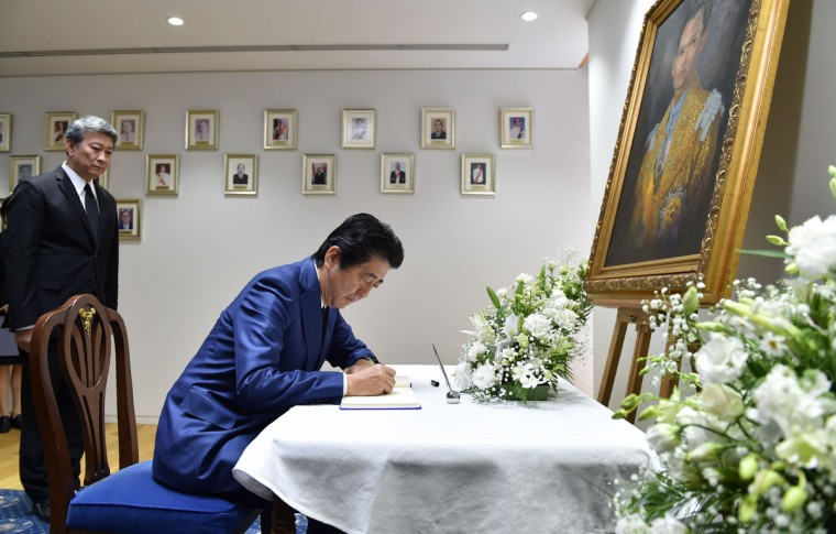 Japan's Prime Minister Shinzo Abe (R) writes his name in a condolence book for the late Thai King Bhumibol Adulyadej at the Thai Embassy in Tokyo on October 14, 2016. Bhumibol, the world's longest-reigning monarch, passed away at 88 on October 13 after years of ill health, removing a stabilising father figure from a country where political tensions remain raw two years after a military coup. / (AFP Photo/Kazuhiro Nogi)