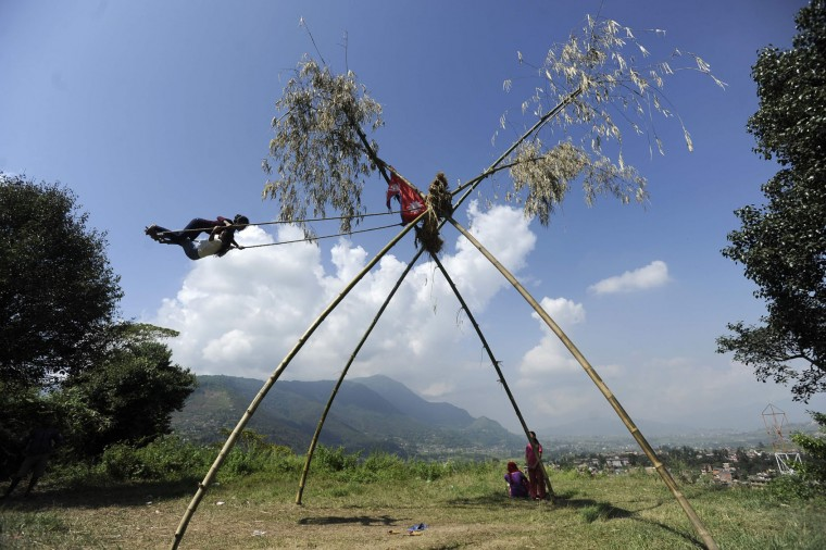"Nepalese youth play on a swing, popularly known as the ""Dashain Ping"", on the sixth day of the Hindu festival of Dashain in Lalitpur, on the outskirts of Kathmandu on October 7, 2016. People of all ages play on a swing in towns and villages, while marking the largest Hindu festival of Dashain in honour of the Hindu goddess of power, Durga. (Prakash Mathema/AFP/Getty Images)"
