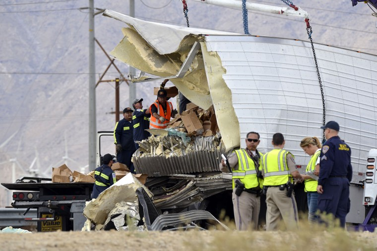 Workers remove debris from a semi-truck that crashed with a tour bus on Interstate 10, west of the Indian Canyon Drive off-ramp, in Desert Hot Springs, near Palm Springs, Calif., Sunday, Oct. 23, 2016. A tour bus and the semi-truck crashed on the highway in Southern California early Sunday, killing at least a dozen of people and injuring at least 30 others, some critically, the California Highway Patrol said. (AP Photo/Rodrigo Pena)