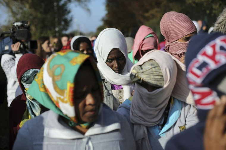 "Women line up to leave the camp and reach England in the makeshift migrant camp known as ""the jungle"" near Calais, northern France, Tuesday, Oct. 25, 2016. Crews have started dismantling the migrant camp in France after the process to clear the camp began in earnest on Monday. (AP Photo/Thibault Camus)"