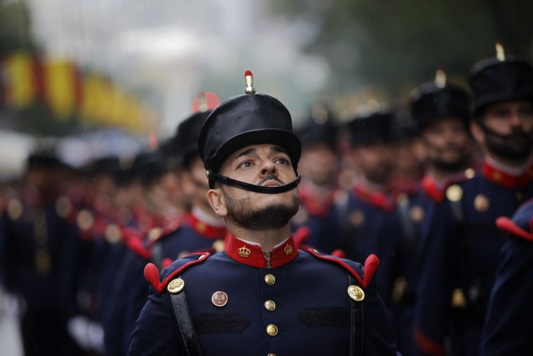 """A Spanish soldier looks up as he marches with others in a military parade during a national holiday known as """"Dia de la Hispanidad"""" or Hispanic Day, in Madrid, Spain, Wednesday, Oct. 12, 2016. Almost a year into Spain's political deadlock, the country is celebrating its National Day with a military parade of over 3,000 soldiers marching through Madrid and aircraft drawing trails of red and yellow smoke in the sky to represent the flag. (AP Photo/Francisco Seco)"""